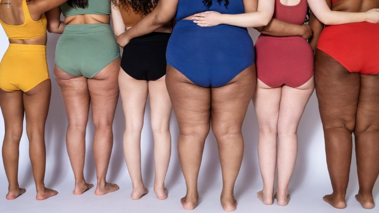 Diverse group of women stand together in brightly coloured lingerie.
