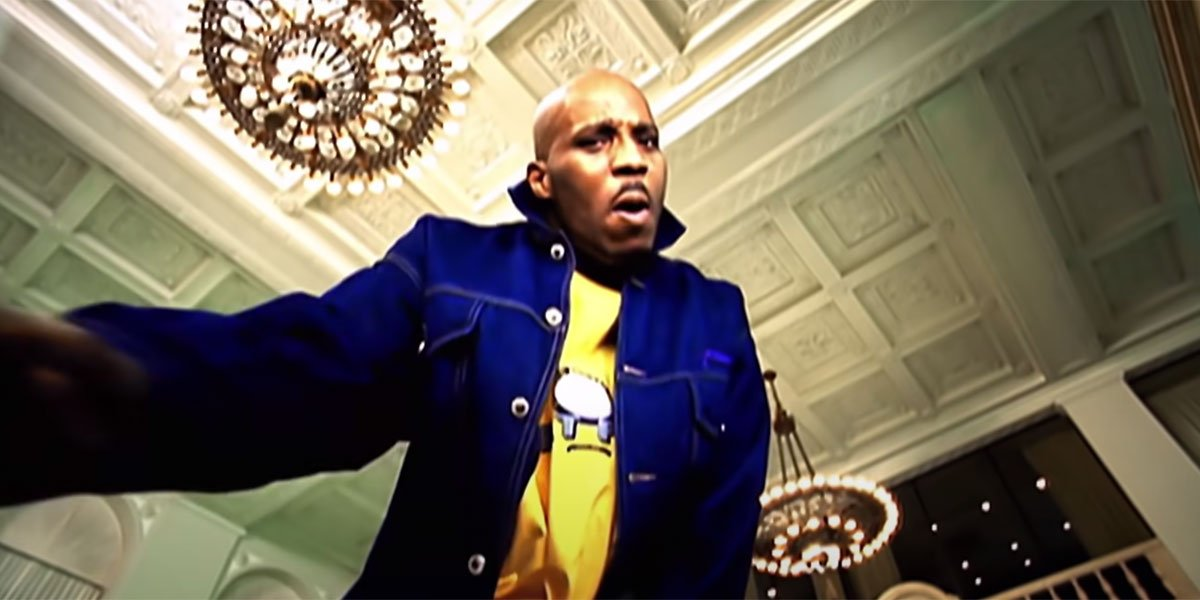 DMX with a yellow shirt on and a white coat inside a bank rapping.