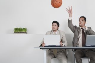 Young businessman watching colleague throwing basketball