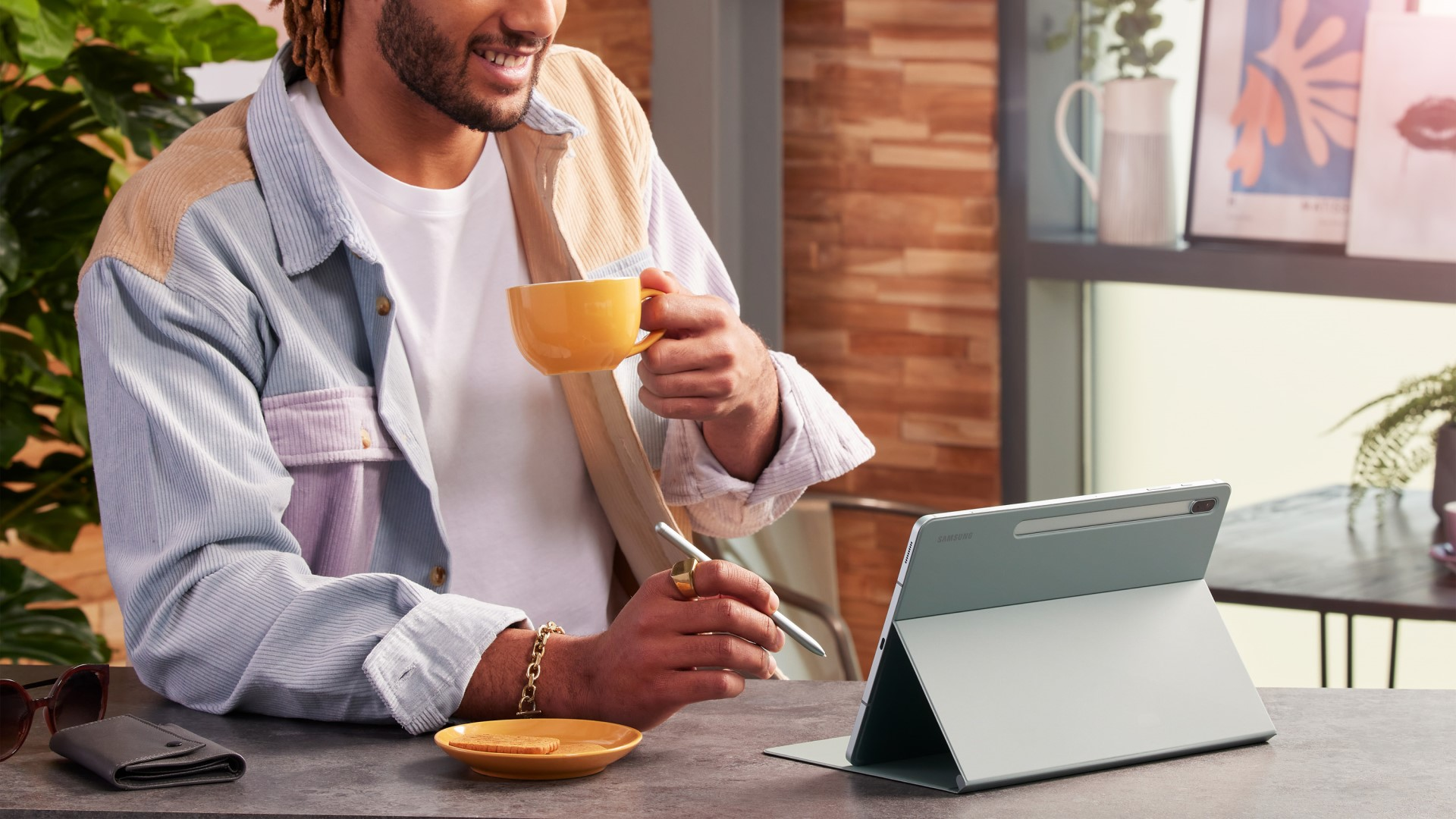 Man drinking from mug, smiling while using Samsung Galaxy Tab S7 FE and S Pen