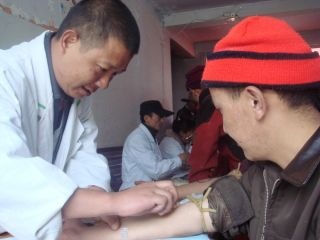 A researcher collects a blood sample from an ethnic Tibetan man participating in a DNA study.