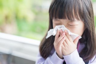 A child with a cold blowing her nose.