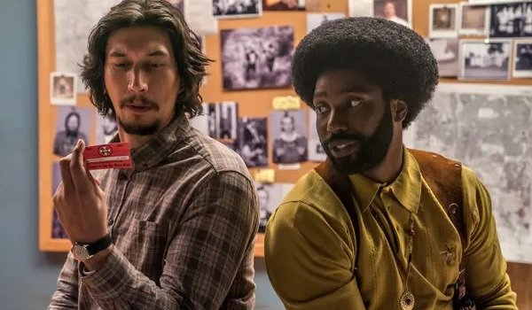 BlacKkKlansman Adam Driver and John David Washington examine a KkK membership card