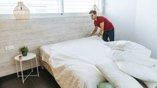 How to wash a mattress protector: A man wearing a red t-shirt removes a white mattress protector from a bed ready for cleaning
