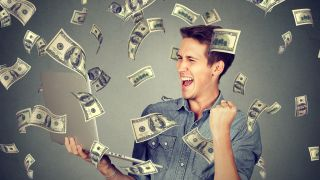 Happy man making money using his laptop
