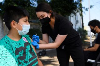 Twelve-year-old Jair Flores receives a first dose of the Pfizer Covid-19 vaccine at a mobile vaccination clinic on May 14, 2021 in Los Angeles, California.
