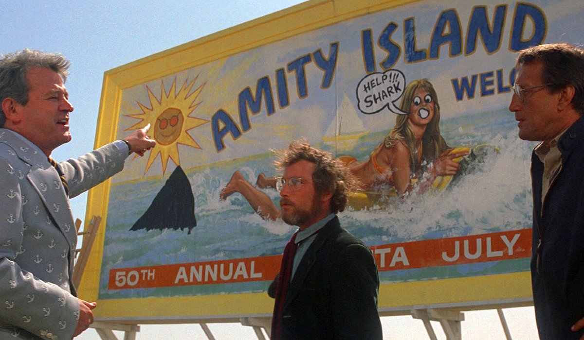 Murray Hamilton, Richard Dreyfuss, and Roy Schieder arguing in front of a billboard in Jaws.