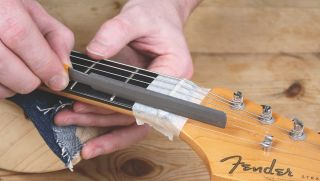 A guitar's nut being repaired