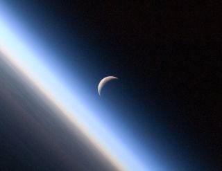 A setting, waning crescent moon amid the thin line of Earth's atmosphere.