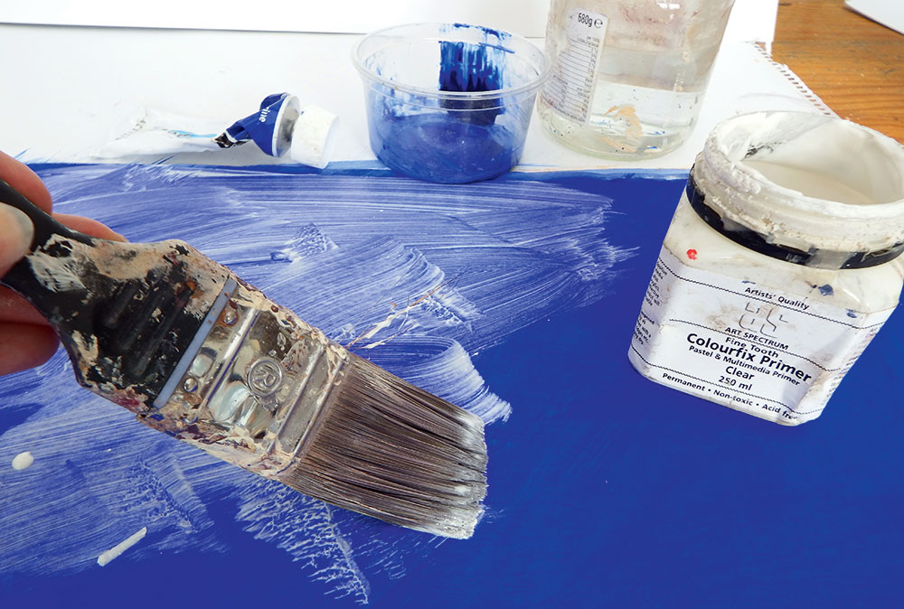 Applying a clear coat of primer to a bright blue surface with a brush