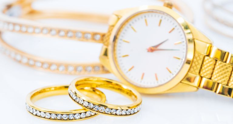 Close-Up of gold watch, diamond rings and bracelet on a table