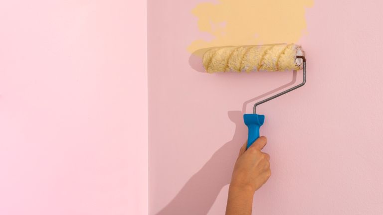 Cropped woman hand painting a wall with a roller applying yellow colored paint to pink wall