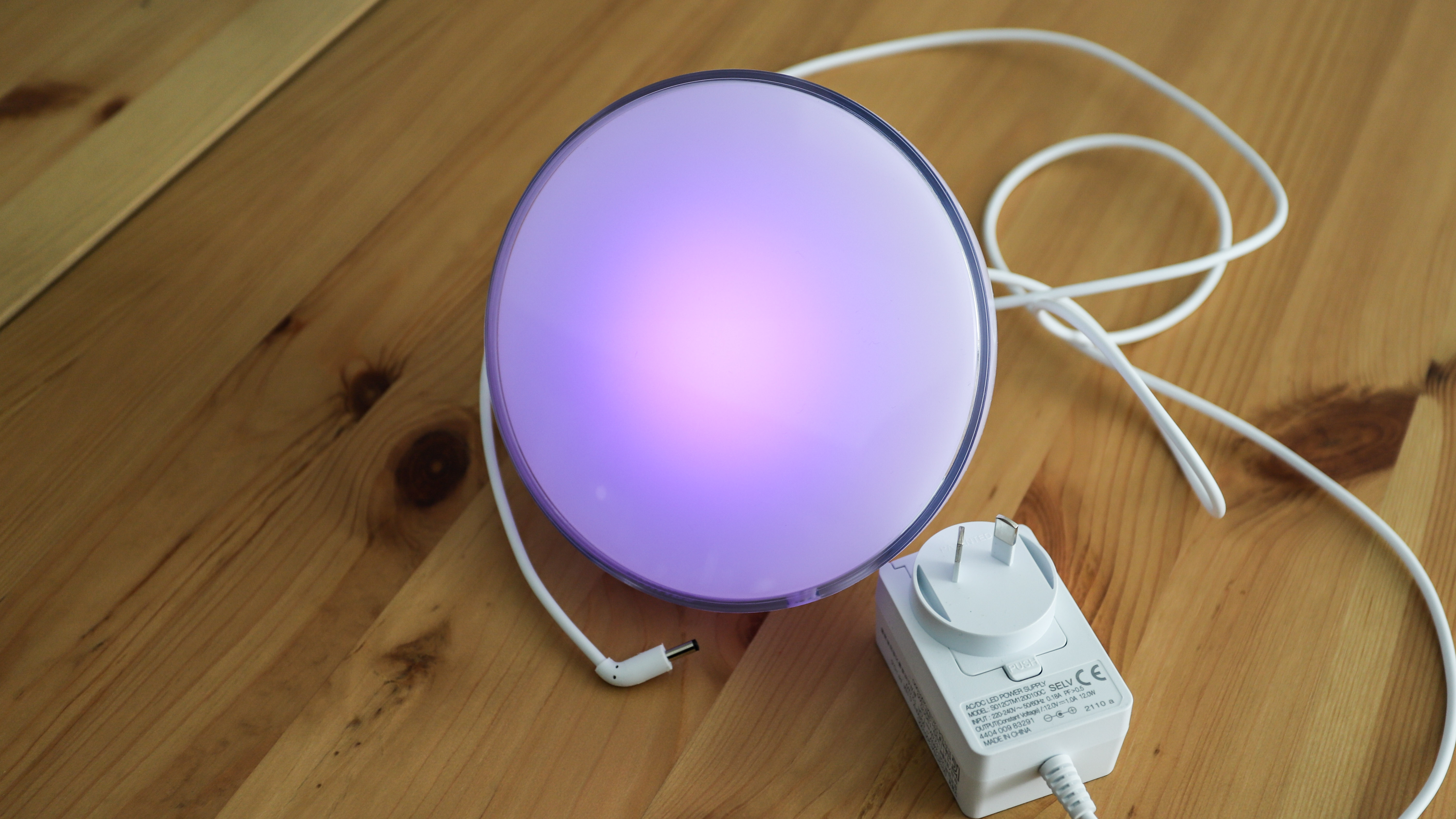 Philips Hue Go 2 in purple light with charger on a table