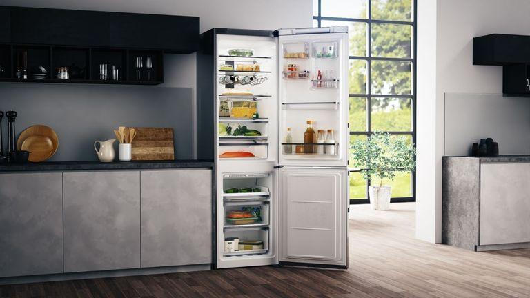 Hotpoint fridge freezer in kitchen with door open and food inside