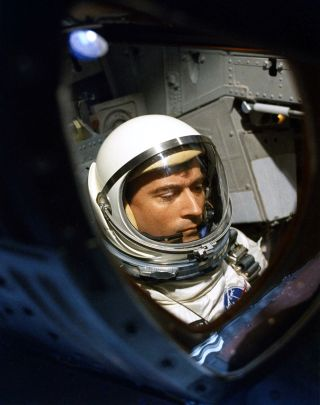 Gemini 3 pilot John Young seen through the hatch window of his spacecraft prior to launch in 1965.