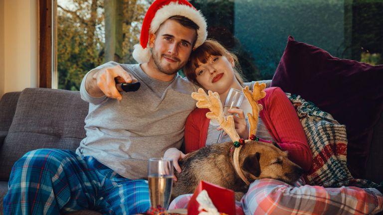 man and woman watching tv at christmas
