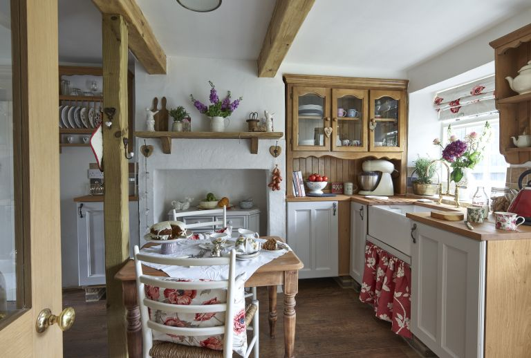english country Kitchens with wooden cabinets, butlers sink, wooden table and chairs and red details
