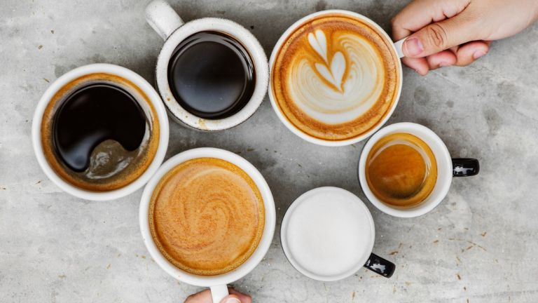 Above Shot Of Hands Holding Coffee Cups On Table