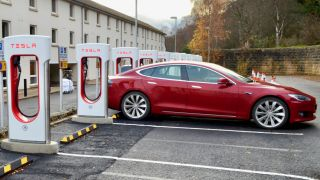 Red Tesla Model S, by charging banks
