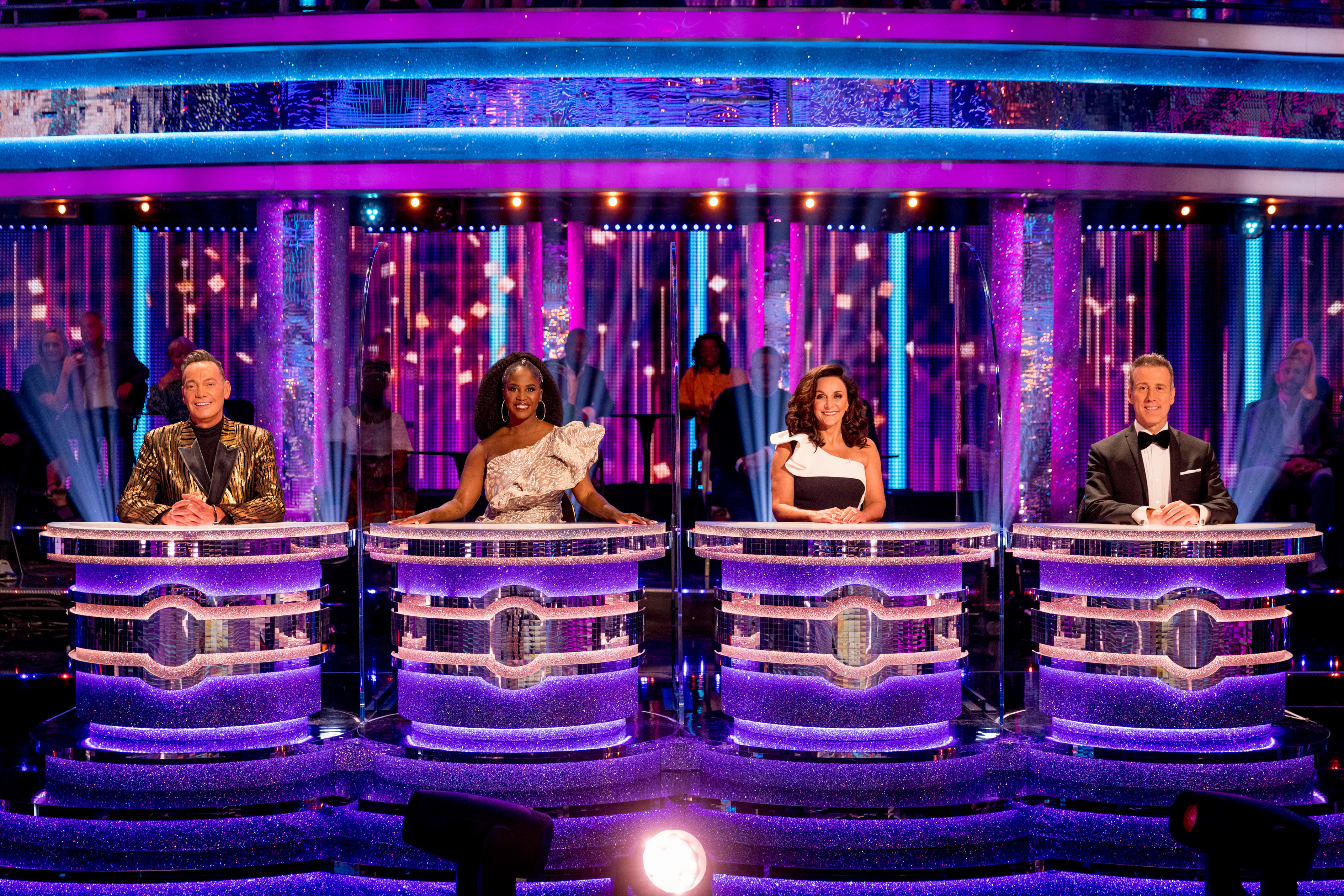 Judges Craig Revel Horwood, Motsi Mabuse, Shirley Ballas, and Anton Du Beke sitting behind their individual desks (divided by transparent screens) in the Strictly studio
