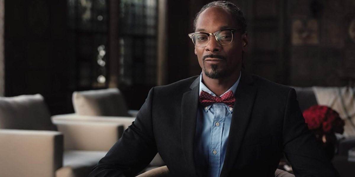 The Black Godfather Snoop Dogg sitting in a chair, wearing a bowtie