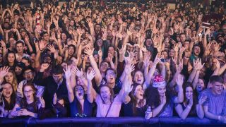 A photograph of a big crowd of young people at a gig