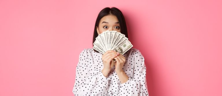 money saving apps - portrait of woman holding paper currency against pink background