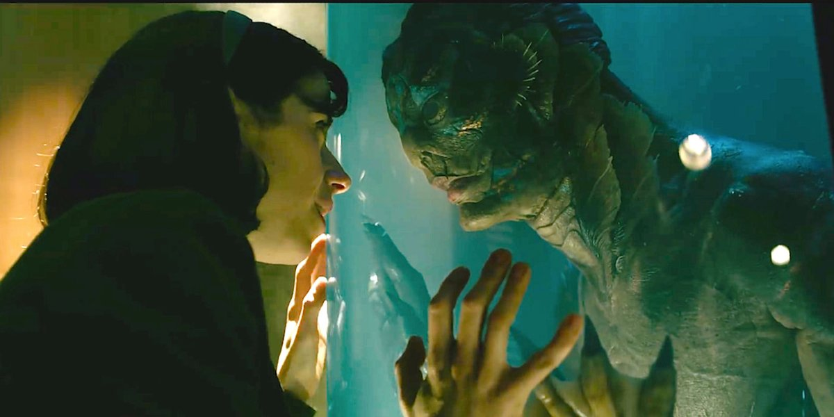 Sally Hawkins and Doug Jones stare at each other through the glass in The Shape of Water.