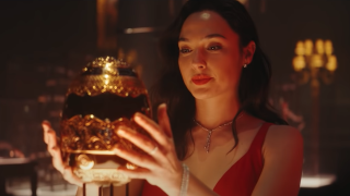 Sarah Black (Gal Gadot) looks pleased as she reaches for an elaborately jeweled egg in 'Red Notice'