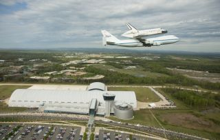 Space shuttle Discovery, mounted atop a NASA 747 Shuttle Carrier Aircraft (SCA) flies over the Steven F. Udvar-Hazy Center, Tuesday, April 17, 2012, in Washington.