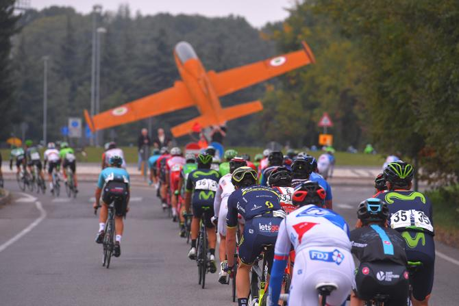 The peloton rides toward the memorial to aircraft engineer Ermanno Bazzocchi in Tradate