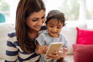 A mom and her toddler play with a smartphone