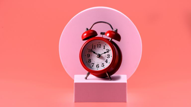 red alarm clock on pink and orange background