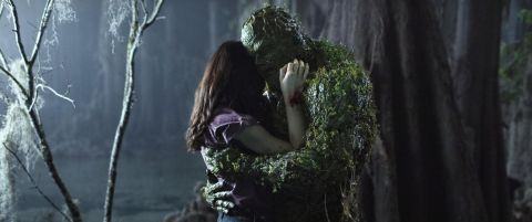 Swamp Thing and Abby Arcane embrace in a dark forest.
