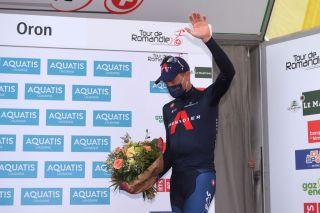 Rohan Dennis (Ineos Grenadiers) steps onto the Tour de Romandie podium after winning the prologue