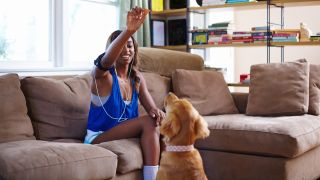 Healthiest dog treats for training: Woman sitting on sofa holding up a treat for her dog