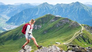 A woman wearing a red backpack hiking in the mountains