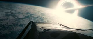 "A spacecraft hangs above an alien planet, with a black hole in the background, in this still from the final trailer for Christopher Nolan's ""Interstellar,"" which opens nationwide on Nov. 7, 2014."
