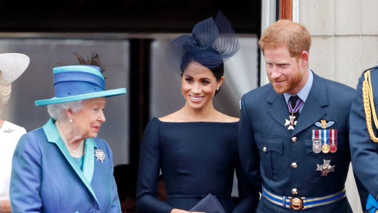 Queen and Meghan, Duchess of Sussex and Prince Harry, Duke of Sussex watch a flypast to mark the centenary of the Royal Air Force from the balcony of Buckingham Palace on July 10, 2018 in London, England.