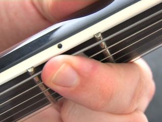 Pressing down near the frets eliminates the possibility of fret-buzz
