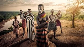 Tribal Africans stood on a mound above river