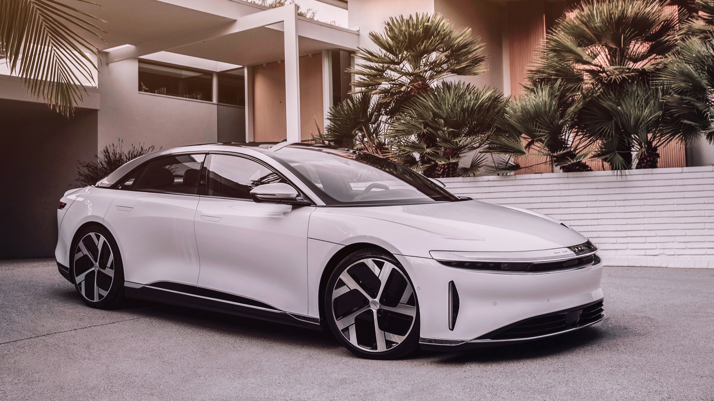 The Lucid Air parked outside a modern house