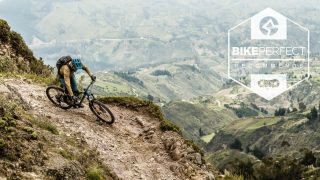 A rider descending an exposed backcountry switchback