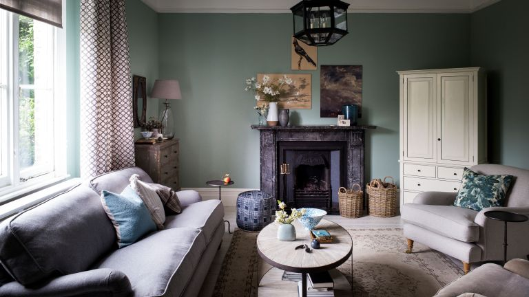Green living room ideas featuring muted green walls, a black fireplace, beige sofas and gallery artwork.