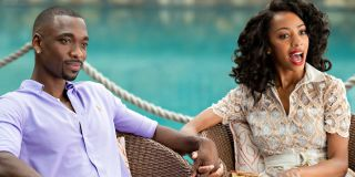 Jay Pharoah and Christiani Pitts sitting at a table holding hands in Resort to Love, he is nervous and she is shocked