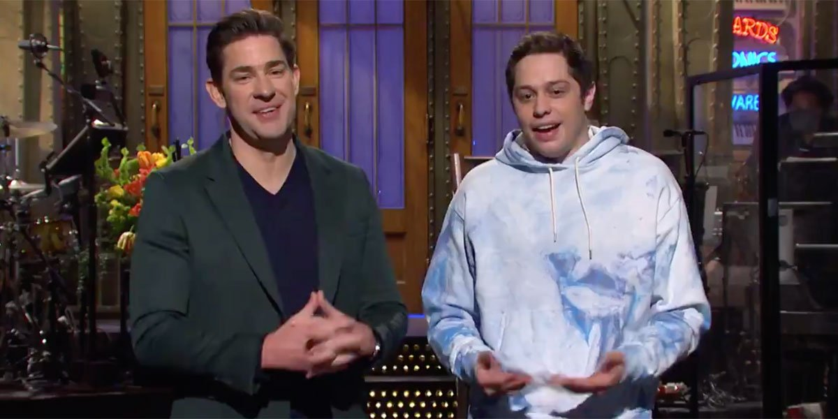 John Krasinski and Pete Davidson talking during the SNL monologue.