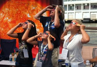 Skywatchers use solar viewing glasses to observe the sun in New York City on July 22, 2012