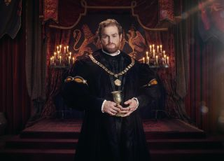 Mark Stanley as King Henry VIII, standing in the throne room holding a golden goblet