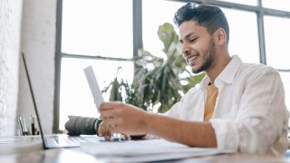 best antivirus software: Smiling man using laptop in front of office window