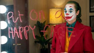 Joaquin Phoenix as Arthur Fleck in clown makeup and 'put on a happy face' on a mirror in red in Joker